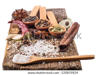 Spices on wooden table with spoons isolated on white background - stock photo