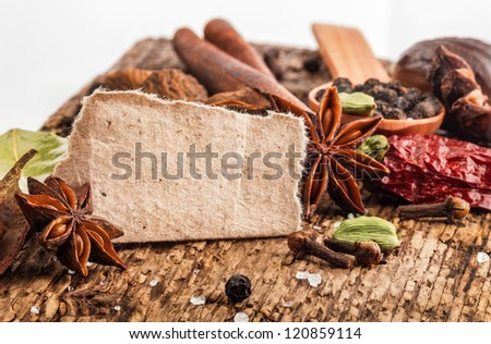 Spices on wooden table with spoons with paper for notes. Spices border - stock photo