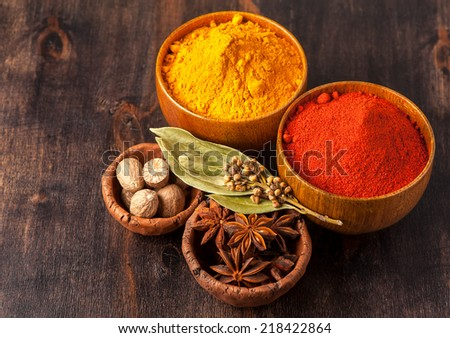 Spices Over Wood.  Curry, paprika, nutmeg, cardamom, bay leaf, anis. - stock photo