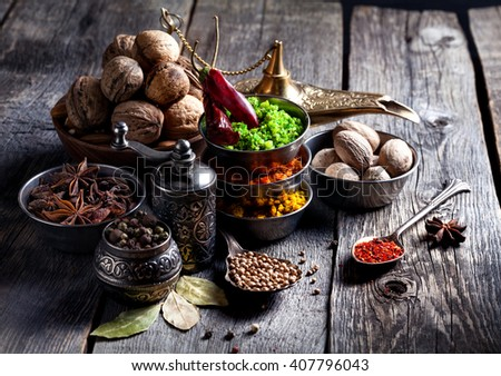 Spices, pepper grinder, spoon with seeds at grey wooden background