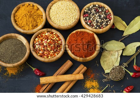 Spices powders and seeds with chili peppers and bay leaves
