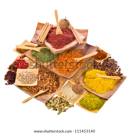 spices powders and solid different colored ground with wooden spoons in a wooden coasters set in a pyramid isolated on white background - stock photo