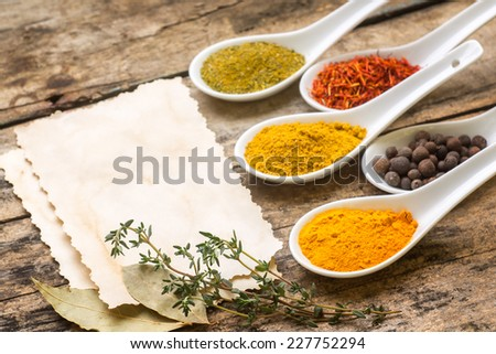 Spices recipe background. Diversity of seasonings with paper sheets on wooden table - stock photo