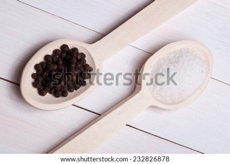 Spices. Rock salt and black pepper on a wooden spoons. - stock photo