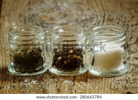 Spices: salt, pepper and herbs in small glass jar on a wooden table, selective focus - stock photo