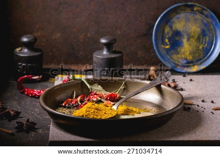 Spices tumeric and dry reh hot chili peppers on metal plate, srved over dark table with vintage weight and blue ceramic plate. - stock photo