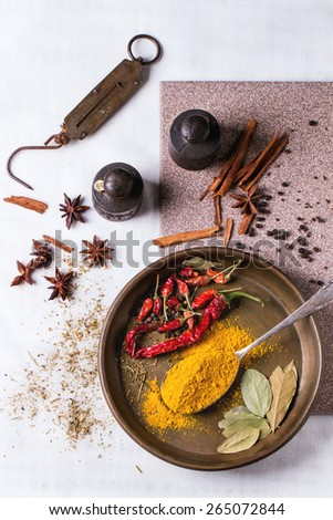 Spices turmeric and dry red hot chili peppers on metal plate, served over white tablecloth with vintage weight. Top view - stock photo
