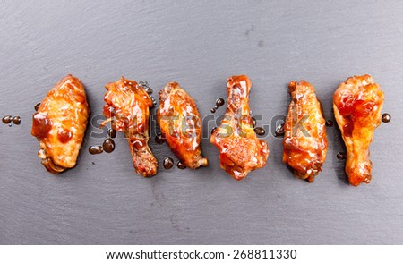 spicy and delicious hot chicken wings in a row - stock photo