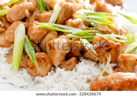 spicy and tangy chicken glazed with orange over white rice with onion - stock photo