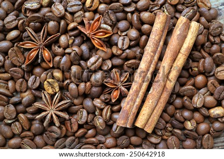 Spicy anise stars and cinnamon sticks on lots of roasted coffee beans - stock photo