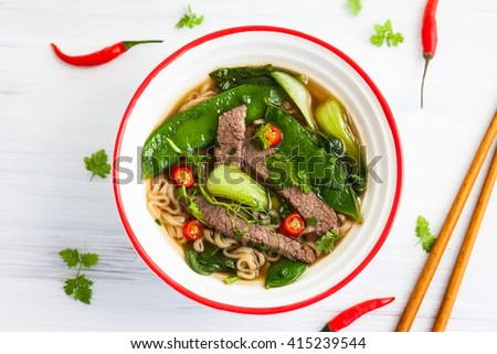 Spicy Asian beef soup with noodles and chinese vegetables - stock photo