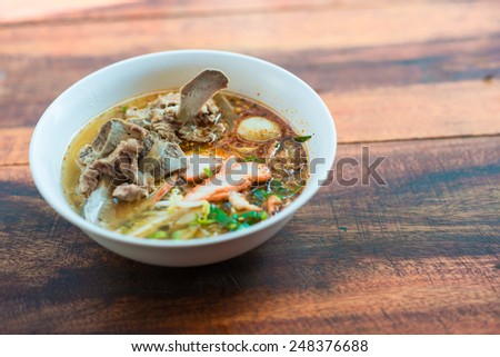 Spicy Asian noodle with pork on wood table, Thai Noodle - stock photo