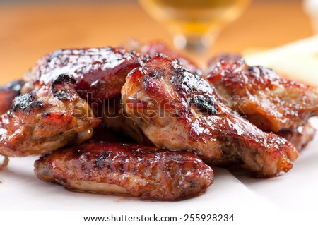 spicy asian style chicken wings with sauce and beer - stock photo