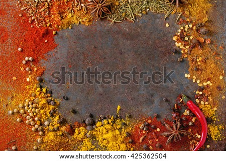 Spicy background with assortment of different hot chili and allspice peppers and mix of other spices over old rusty iron background. Top view. With space for text