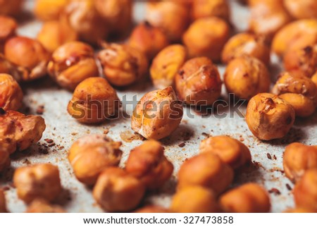 Spicy baked chickpeas scattered on  baking paper - stock photo