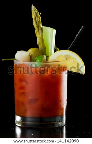 spicy Bloody Mary served on a dark bar garnished with pickled veggies and a lemon - stock photo