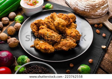 Spicy breaded chicken wings with homemade bread, all homemade - stock photo