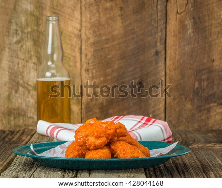 Spicy buffalo style chicken wings on a tin plate. - stock photo