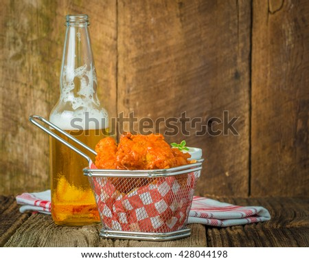 Spicy buffalo style wings in a basket served with cold beer. - stock photo