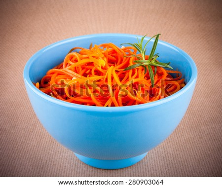 Spicy carrot salad in blue bowl on brown background - stock photo