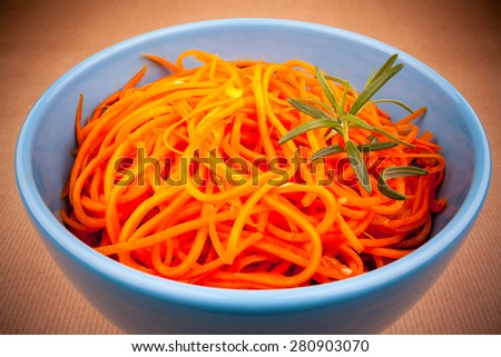 Spicy carrot salad in blue bowl on brown background, vignette, close up - stock photo