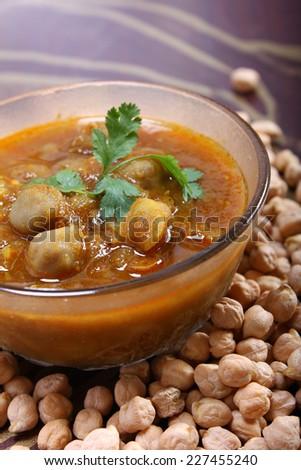 spicy chana masala, raw chickpeas around the bowl indian dish - stock photo