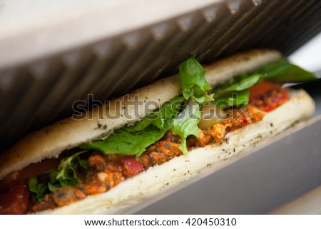 Spicy chicken, olives, baby corn, tomatoes and lettuce baguette in a toaster in a cafe - stock photo