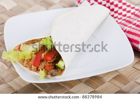 Spicy chicken with salad wrapped in a soft flour tortilla. - stock photo