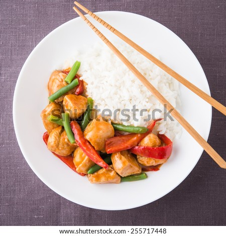 Spicy chicken with vegetables ( green beans and red pepper) and rice on dark canvas background top view. Oriental food. - stock photo