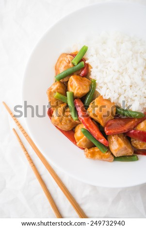 Spicy chicken with vegetables ( green beans and red pepper) and rice on white paper background top view. Oriental food. - stock photo