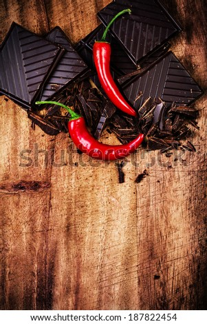 Spicy Chocolate Bar with Red Chilli Pepper on wooden background closeup. Chunks of Broken dark chocolate bar on wood table macro. - stock photo