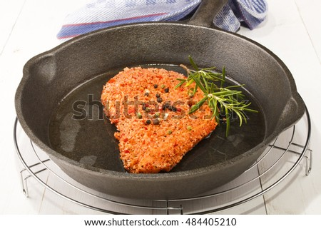 spicy coated pork chop with peppercorn in a cast iron pan