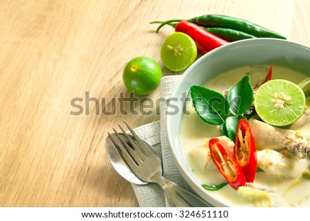 Spicy creamy coconut soup with chicken , Thai food called Tom Kha Gai on wooden table - stock photo