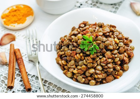 spicy curry cinnamon green lentils on a white background. the toning. selective focus - stock photo