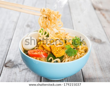 Spicy curry instant noodles with chopsticks. Asian cuisine, ready to serve on wooden dining table setting. Fresh hot with steamed smoke.