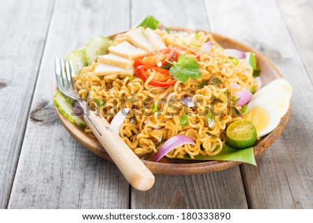 Spicy fried curry instant noodles or Malaysian style maggi goreng mamak.  Asian cuisine, ready to serve on wooden dining table setting. Fresh hot with steamed smoke. - stock photo