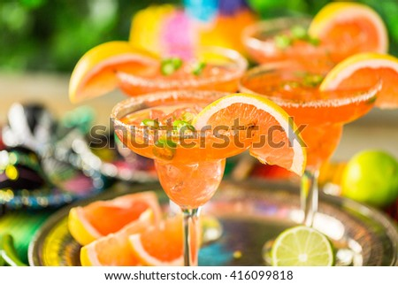 Spicy grapefruit margarita on ice in margarita glasses on the table in the garden.