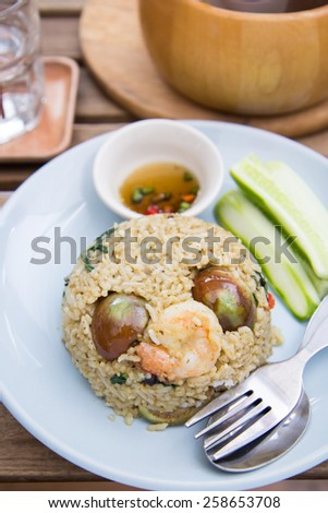Spicy green curry fired rice with shrimps on wooden table - stock photo