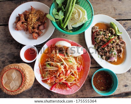 Spicy green papaya salad, spicy duck salad, fried pork (traditional thai food) - stock photo