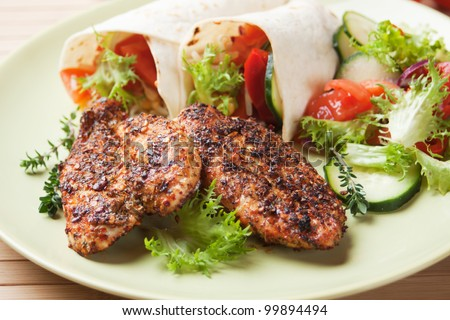 Spicy grilled chicken meat with fresh vegetable salad