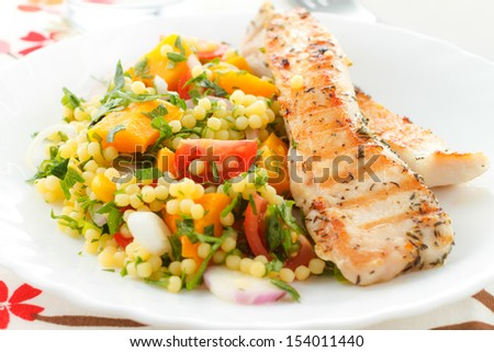Spicy grilled chicken with fresh vegetables and couscous - stock photo