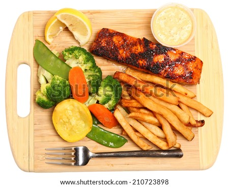 Spicy grilled salmon steak with steamed vegetables, french fries, lemon wedges and tartar sauce. Served on cutting board. Isolated, high angle view. - stock photo