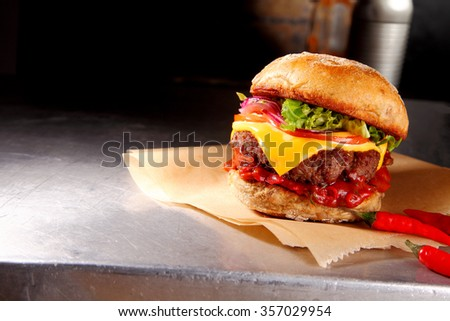 Spicy hot chili cheeseburger with a juicy beef patty topped with melted cheese and salad trimmings on a crusty bun, rustic setting with copyspace - stock photo