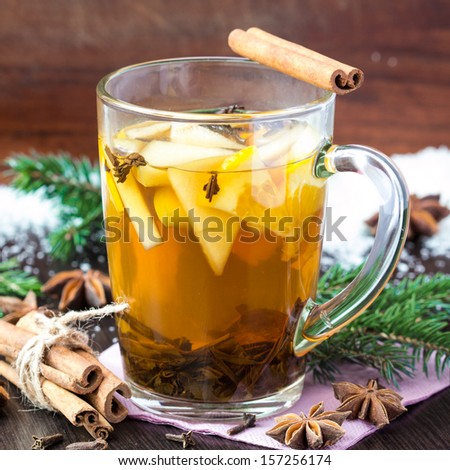 Spicy hot tea with apple and orange, cinnamon, star anise, Christmas drink - stock photo