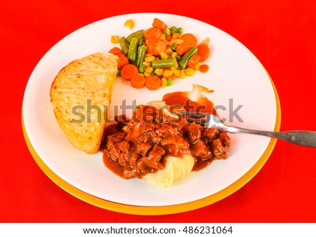 Spicy Hungarian Goulash over mashed potatoes against bright red background.