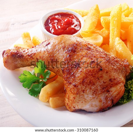 Spicy marinated and seasoned chicken drumstick or thigh with French fries and tomato ketchup for a tasty meal - stock photo