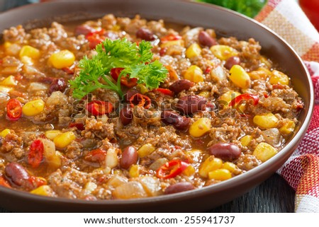 spicy Mexican dish chili con carne in a brown pottery plate, close-up, horizontal