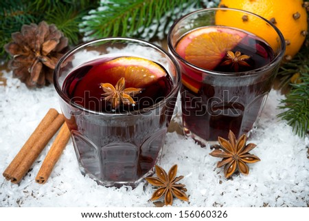 spicy mulled wine in glasses on the snow, horizontal