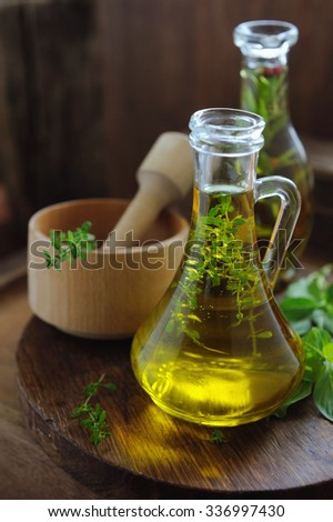 Spicy oils with herbs and spices in different bottles and green basil on wood rustic table - stock photo
