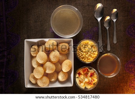Spicy pani puri or golgappa is an Indian chat or snack item, shown with accompaniments on the side